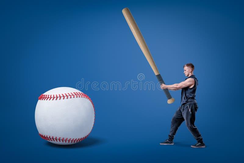 Zijaanzicht die van de jonge atletische mens in gymnastiekkostuum, enorme knuppel houden en klaar om reusachtig honkbal te raken stock foto