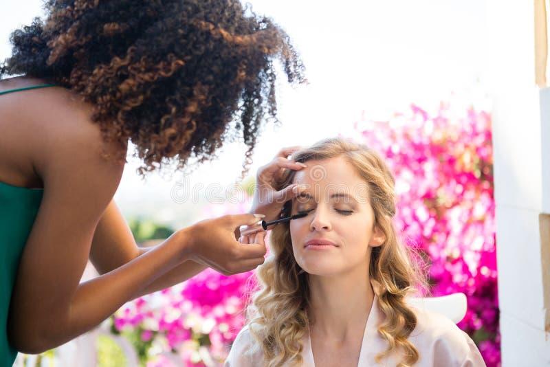 Zijaanzicht die van schoonheidsspecialist mascara toepassen op bruid royalty-vrije stock fotografie