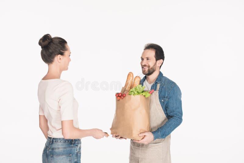 zijaanzicht die van vrouw creditcard geven aan winkelmedewerker in schort met document pakkethoogtepunt van voedsel stock foto