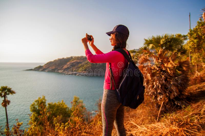 Zijaanzicht die van vrouw met rugzak en smartphone foto op zee op heuvel nemen tegen hemel stock foto's
