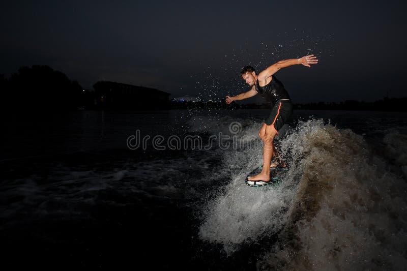 Zijaanzicht jong personenvervoer op wakeboard in de nacht royalty-vrije stock fotografie