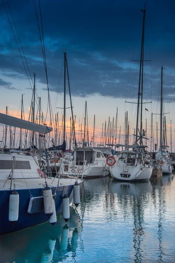 Zijaanzicht over vastgelegde zeilboten in de clubhaven van het Jachthavenjacht van Montgat bij zonsondergang met dramatische bewo stock foto