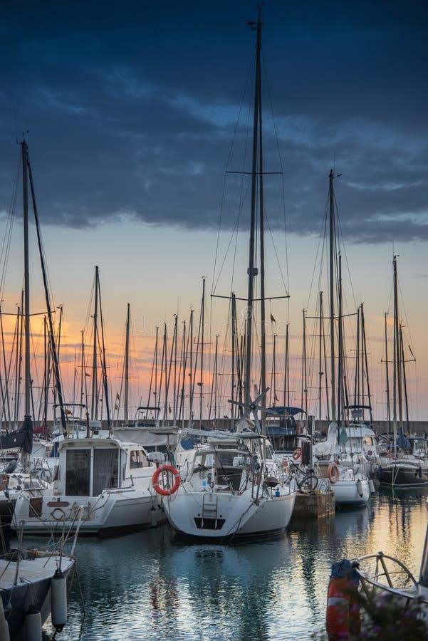 Zijaanzicht over vastgelegde zeilboten in de clubhaven van het Jachthavenjacht van Montgat bij zonsondergang met dramatische bewo royalty-vrije stock afbeelding
