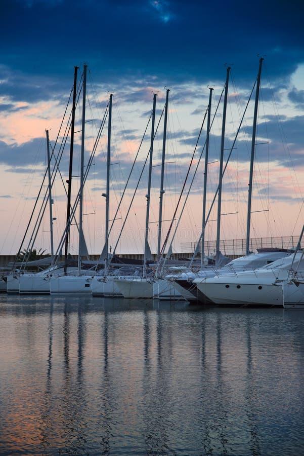 Zijaanzicht over vastgelegde zeilboten in de clubhaven van het Jachthavenjacht van Montgat bij zonsondergang met dramatische bewo royalty-vrije stock foto's