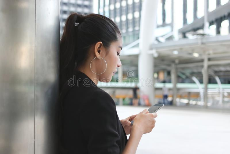 Zijaanzicht van aantrekkelijke jonge Aziatische vrouw die mobiele slimme telefoon op de straat van stad houden Sociaal netwerkcon royalty-vrije stock foto