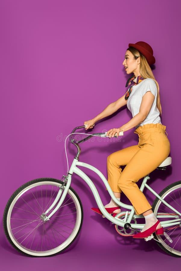 zijaanzicht van aantrekkelijke modieuze Aziatische meisje berijdende fiets en weg het kijken royalty-vrije stock afbeeldingen