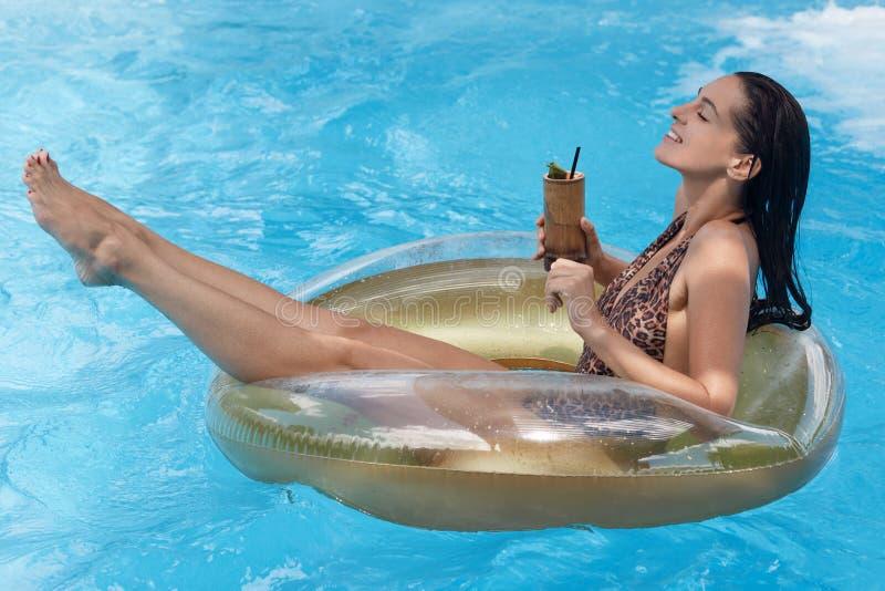 Zijaanzicht van aantrekkelijke slanke gelooide vrouwenzitting op zwemmende ring, houdend cocktail in hand en ontspannend bij de t stock fotografie