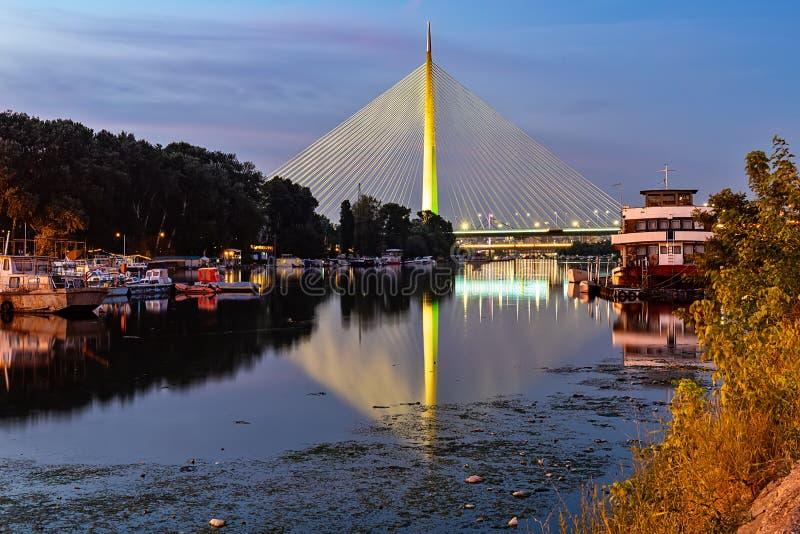 Zijaanzicht van Ada brug bij nacht met bezinning over de jachthaven van Belgrado op Sava-rivier royalty-vrije stock foto
