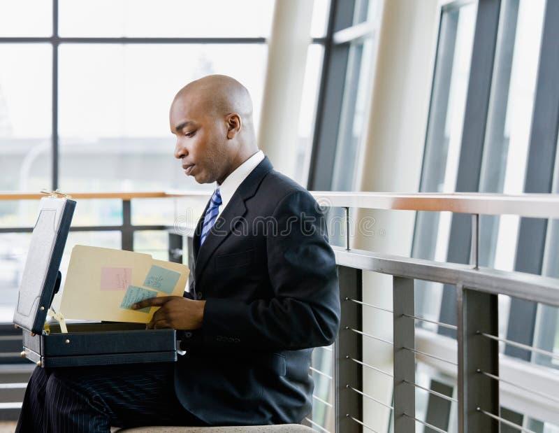 Zijaanzicht van Afrikaanse zakenman het herzien dossiers stock fotografie