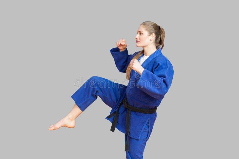 Zijaanzicht van agressieve atletische karatevrouw in blauwe kimono met royalty-vrije stock afbeelding