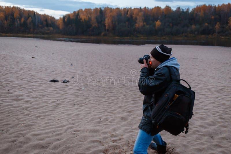 Zijaanzicht van amateurfotograaf die het de herfstlandschap van de bosweg schieten Landschapstherapie stock fotografie