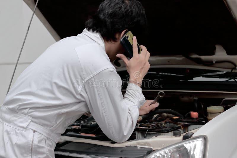 Zijaanzicht van automobielhersteller in het eenvormige spreken op telefoon en het onderzoeken van motor onder kap van auto bij de royalty-vrije stock afbeeldingen