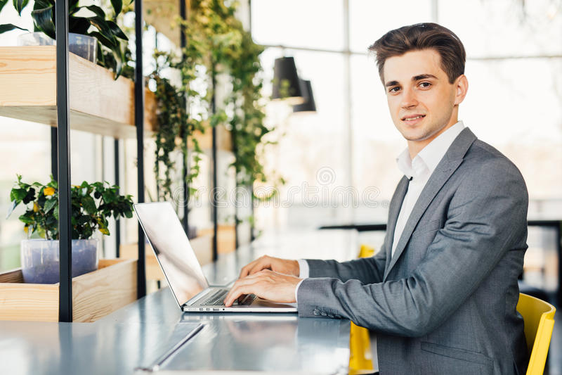 Zijaanzicht van bedrijfsmensenzitting door de lijst met laptop computer en het bekijken camera royalty-vrije stock foto's