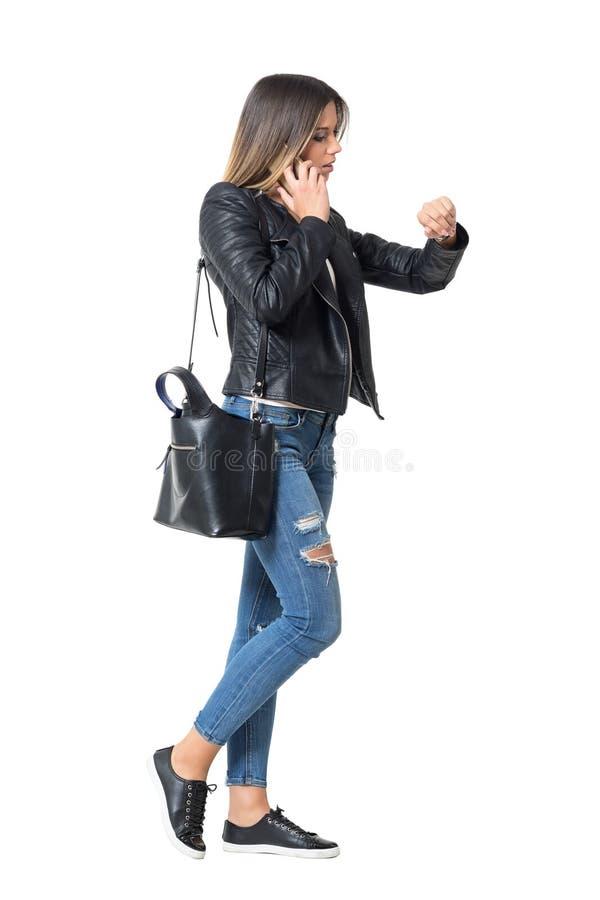 Zijaanzicht van bezig toevallig maniermeisje op de telefoon die tijd controleren op haar horloge stock foto