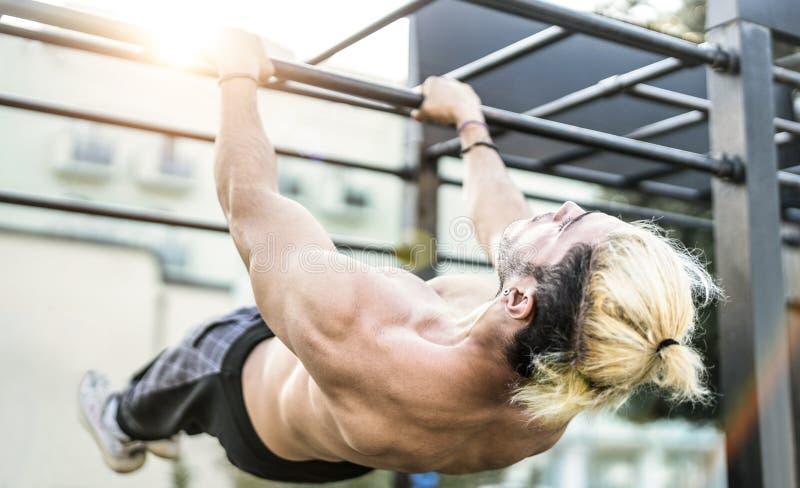 Zijaanzicht van de atletische mens die de beweging van de gymnastiektraining op rekstok uitoefenen in openlucht - het Moderne alt stock foto