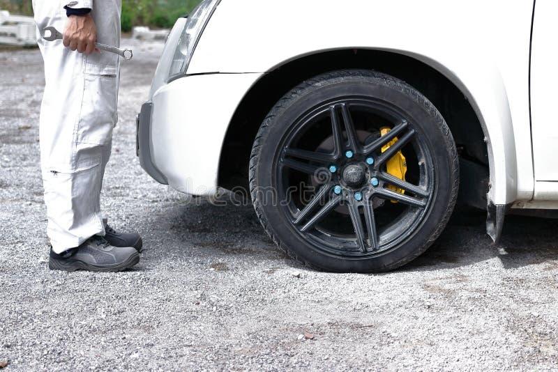 Zijaanzicht van de automobiel mechanische mens in witte eenvormige holdingsmoersleutel in zijn handen klaar aan het herstellen va stock foto