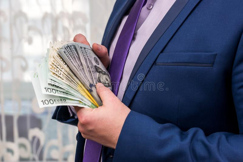 Zijaanzicht van de euro en de dollarbundel van de zakenmanholding royalty-vrije stock foto