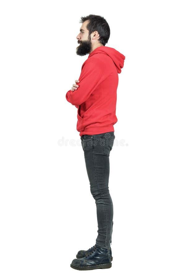 Zijaanzicht van de gebaarde jonge mens die in rode hoodie met gekruiste wapens weg kijken royalty-vrije stock foto's
