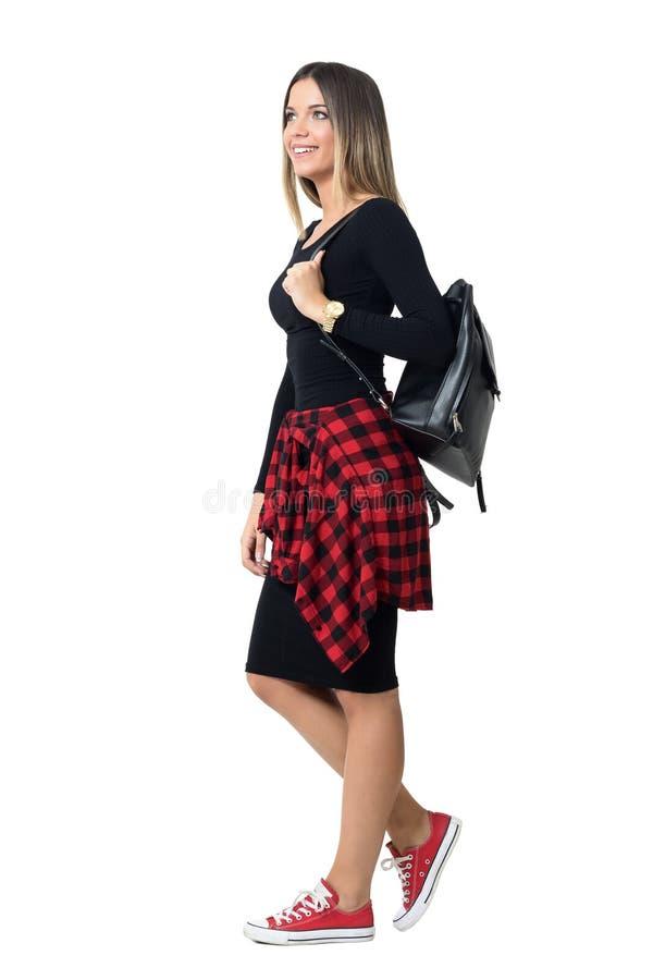 Zijaanzicht van de jonge dragende en zak die van het studenten modieuze meisje naar boven gaan eruit zien royalty-vrije stock afbeeldingen