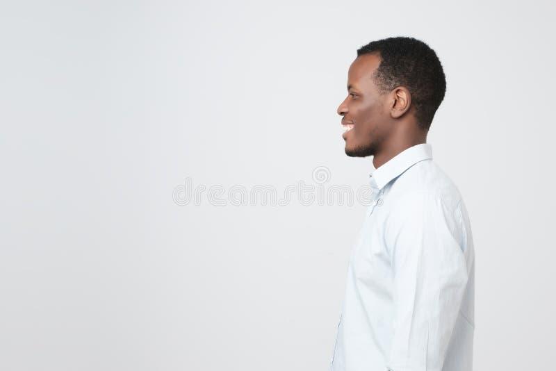 Zijaanzicht van de jonge gelukkige Afrikaanse glimlachende mens stock afbeeldingen
