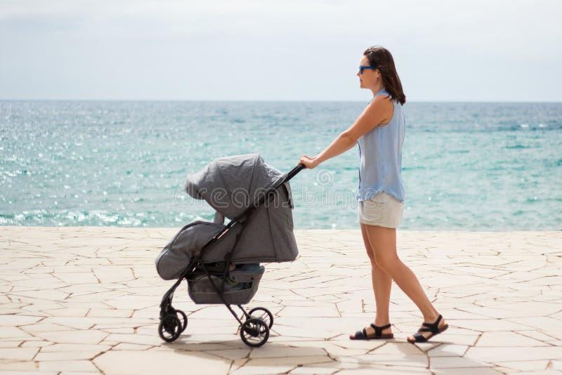 Zijaanzicht van de jonge wandelwagen van de moeder duwende baby stock afbeelding