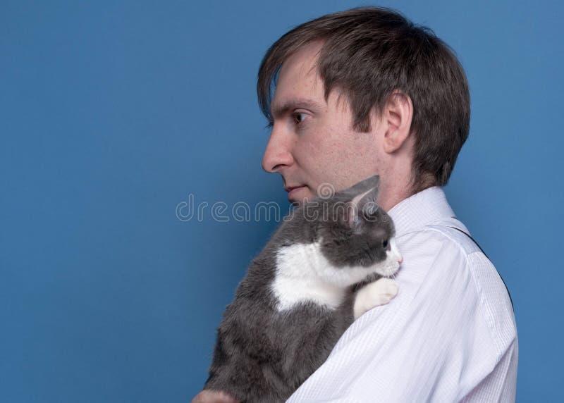 Zijaanzicht van de knappe mens in roze overhemd die aanbiddelijke grijze kat op schouder houden royalty-vrije stock foto's