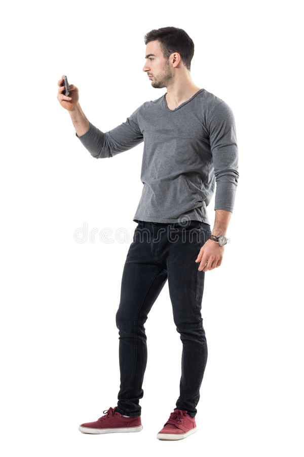Zijaanzicht van de koele ontspannen jonge toevallige mens die beeld met mobiele telefoon nemen royalty-vrije stock foto's