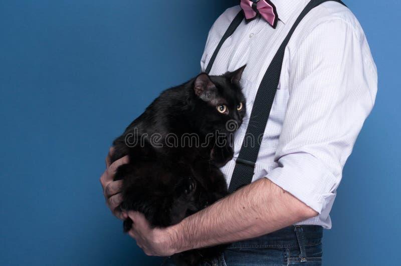 zijaanzicht van de mens in overhemd, bretel en roze vlinderdas die leuke zwarte kat op blauwe achtergrond houden stock foto