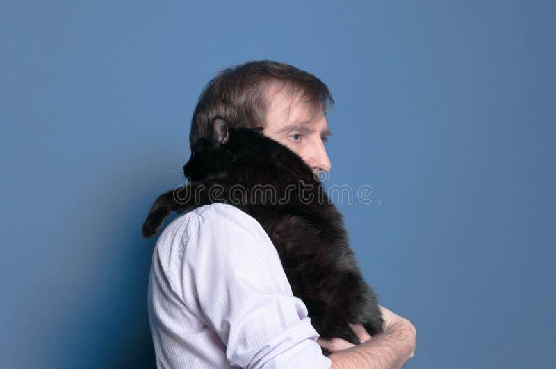 Zijaanzicht van de mens in overhemd die zwarte leuke kat op schouder houden royalty-vrije stock afbeelding