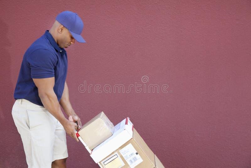 Zijaanzicht van de spier Afrikaanse Amerikaanse leveringsmens met handtruck stock afbeeldingen