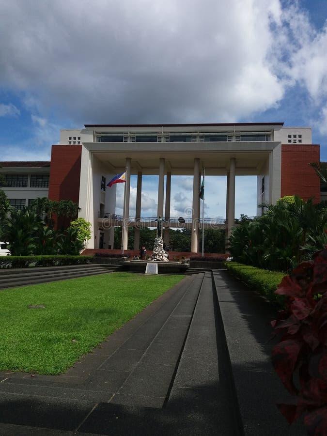 Zijaanzicht van de tuin van het Oblatiestandbeeld van Universiteit van de Filippijnen met erachter Zaal stock foto