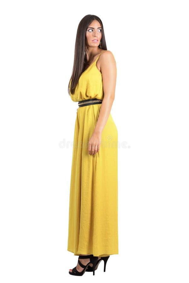 Zijaanzicht van doen schrikken mannequin in gele avondjurk die achter over haar schouder kijken royalty-vrije stock foto