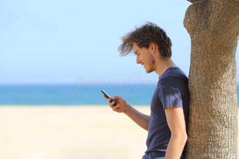 Zijaanzicht van een aantrekkelijke mens die een slimme telefoon op het strand met behulp van stock afbeelding