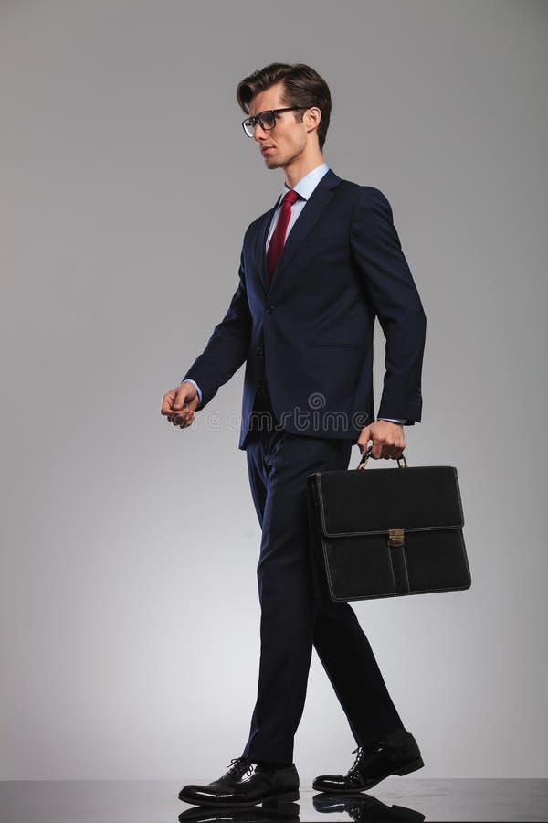 Zijaanzicht van een elegante aktentas van de zakenmanholding en walkin stock foto