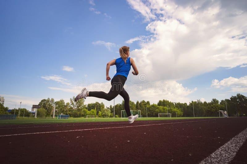 Zijaanzicht van een geschikte jonge vrouwenjogging bij het stadion Een jonge atletenlooppas in sportkleding bij het stadion in de stock foto
