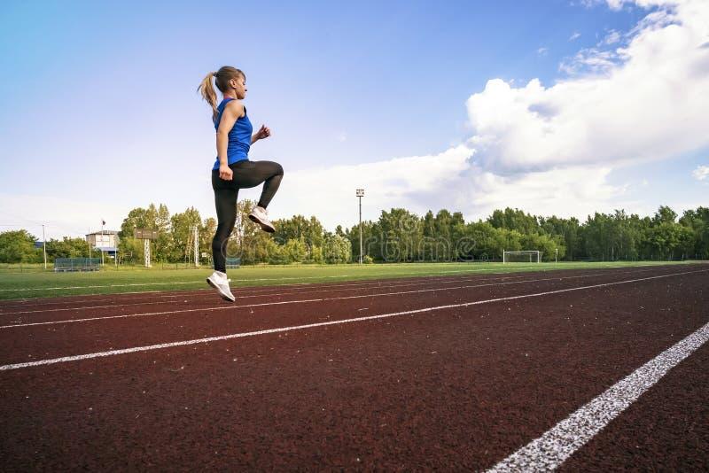 Zijaanzicht van een geschikte jonge vrouwenjogging bij het stadion Een jonge atletenlooppas in sportkleding bij het stadion in de royalty-vrije stock foto