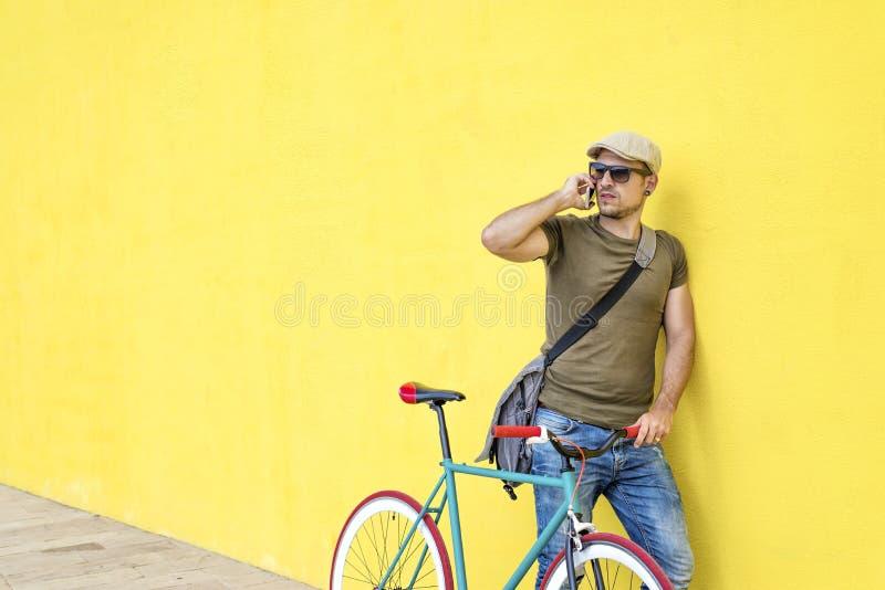 Zijaanzicht van een jonge volwassen mens met een uitstekende fiets en het dragen van vrijetijdskleding en zonnebril die zich tege royalty-vrije stock foto's