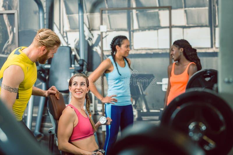 Zijaanzicht van een knappe persoonlijke trainer die zijn cliënt begeleiden bij de gymnastiek stock fotografie