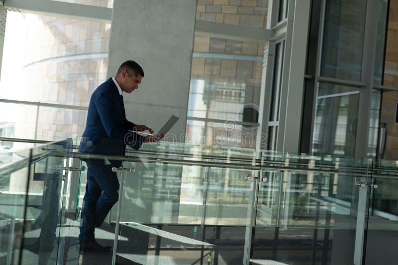 Zijaanzicht van een knappe zakenman die aan zijn laptop op de parterregang werken van het bureau stock foto