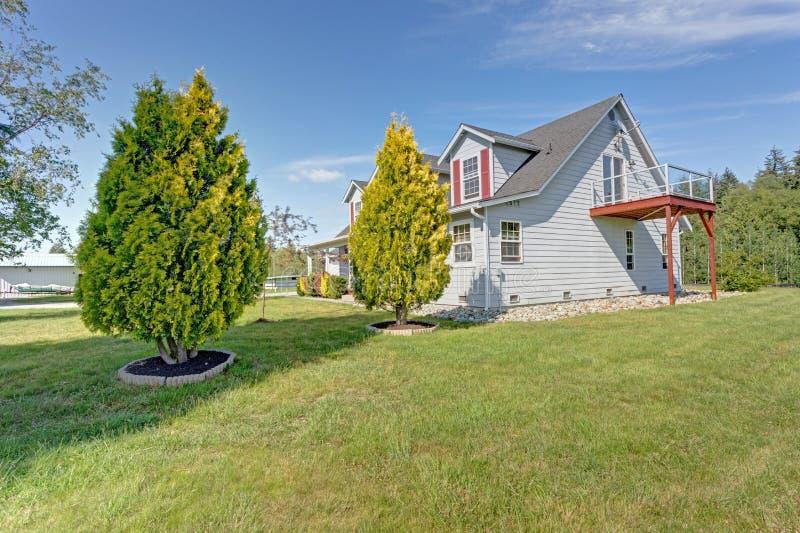 Zijaanzicht van een lichtblauw huis met groen gazon rond het stock afbeeldingen