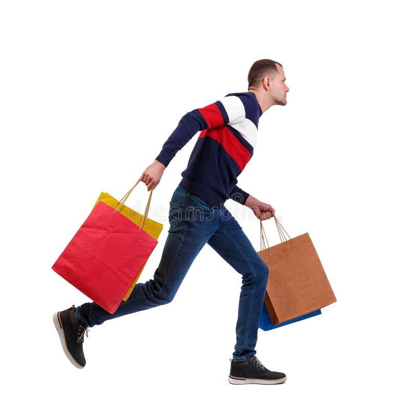 Zijaanzicht van een mens in een sweater met het winkelen zakken die loopt stock fotografie