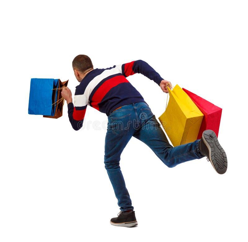 Zijaanzicht van een mens in een sweater met het winkelen zakken die loopt stock afbeelding