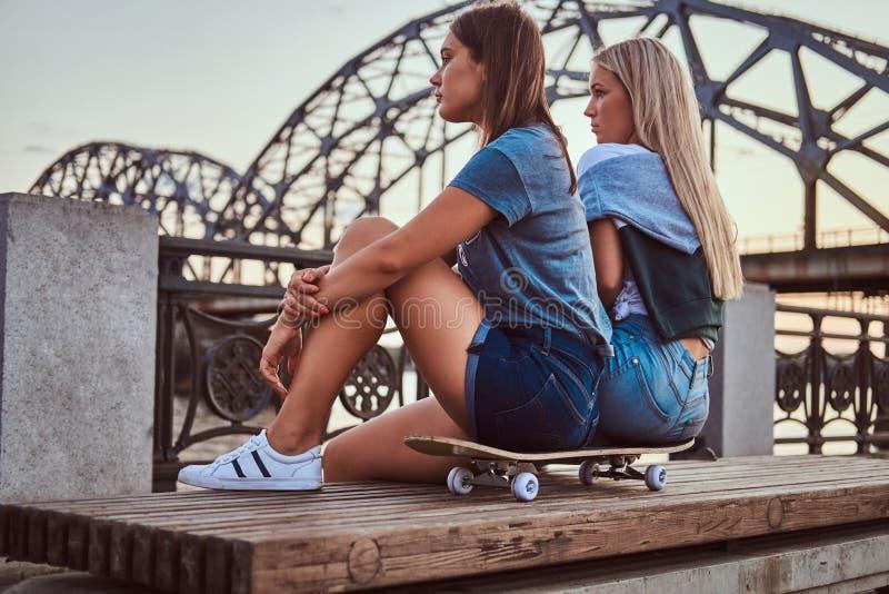 Zijaanzicht van een twee jonge hipstermeisjes die op een skateboard zitten en weg op achtergrond van de oude brug bekijken bij stock foto