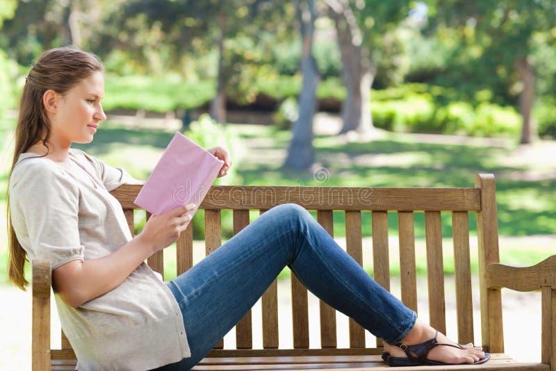 Zijaanzicht van een vrouw die een roman op een parkbank lezen royalty-vrije stock foto