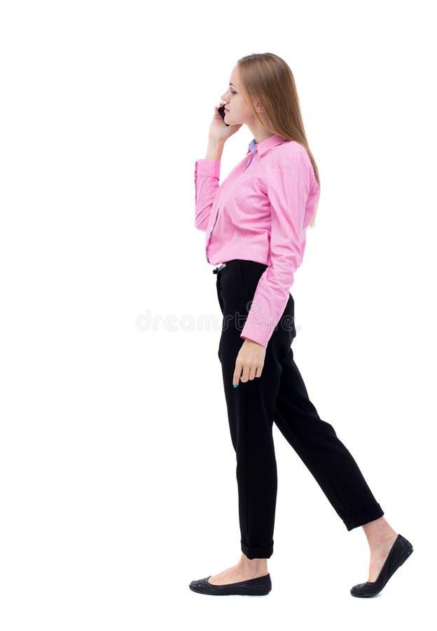 Zijaanzicht van een vrouw die met een mobiele telefoon lopen achtermeningsofgi stock foto's