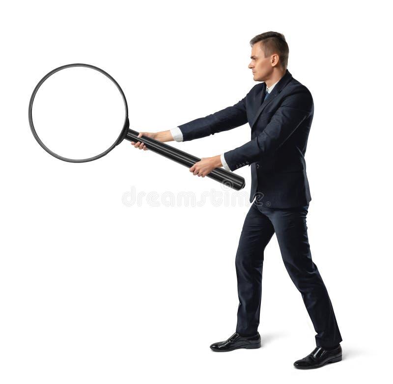 Zijaanzicht van een zakenman die grote meer magnifier met beide die handen houden op witte achtergrond worden geïsoleerd royalty-vrije stock afbeelding