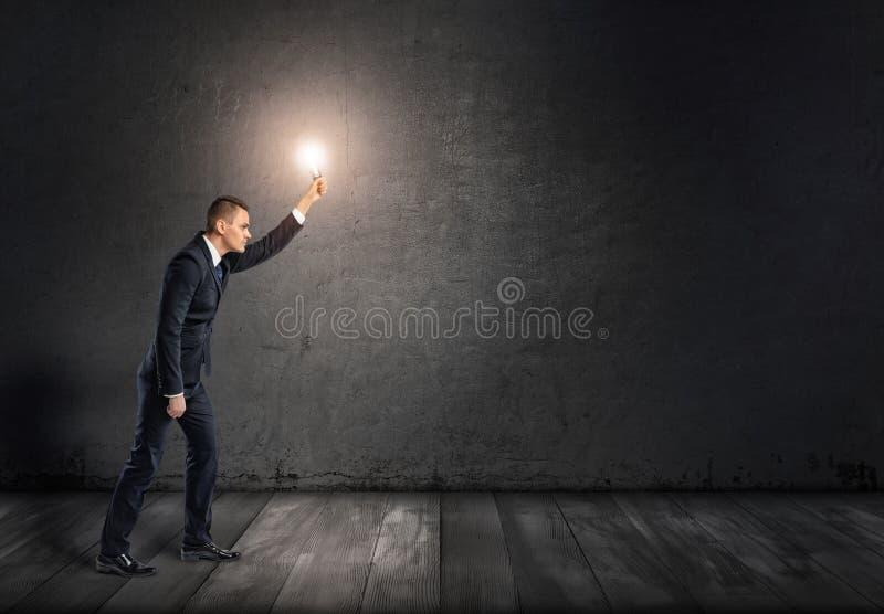 Zijaanzicht van een zakenman met gloeiende gloeilamp in uitgestrekt wapen die door duisternis gaan royalty-vrije stock foto's