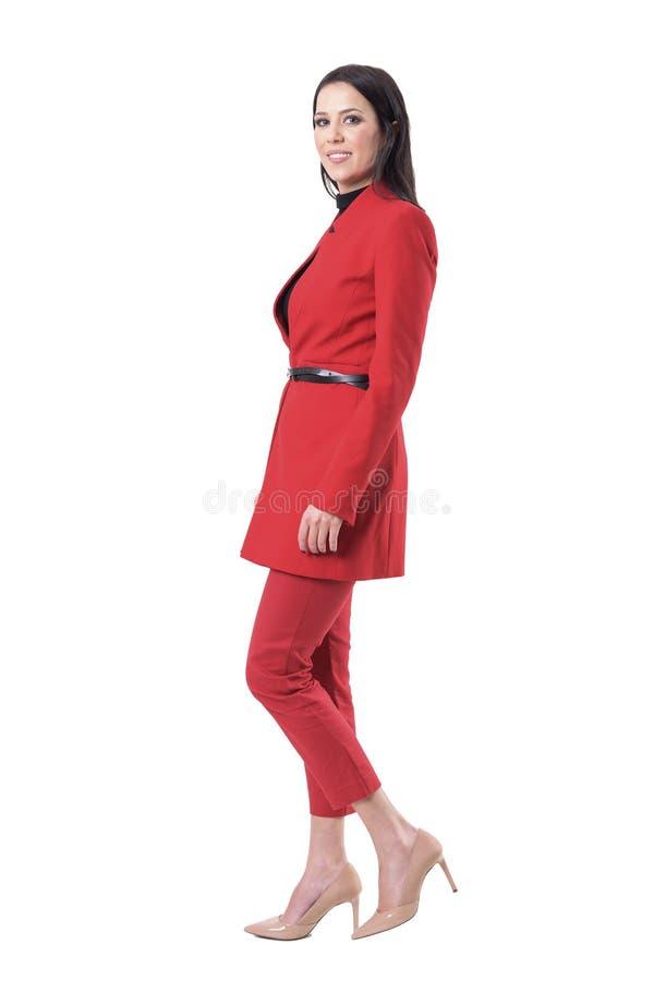 Zijaanzicht van elegante bedrijfsvrouw in rood kostuum die en bij camera lopen glimlachen royalty-vrije stock foto's