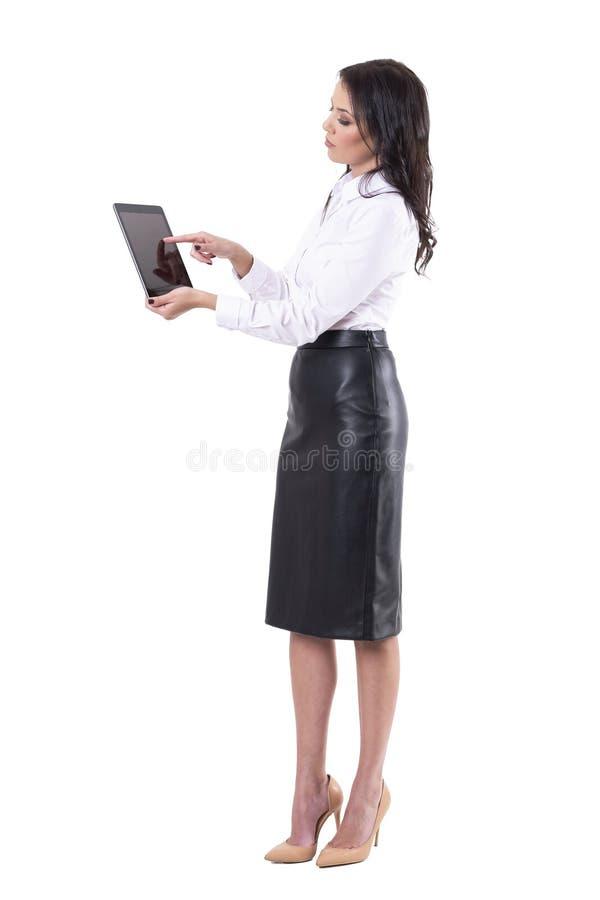 Zijaanzicht van elegante jonge bedrijfsvrouw die interactief tablettouch screen met behulp van stock afbeeldingen