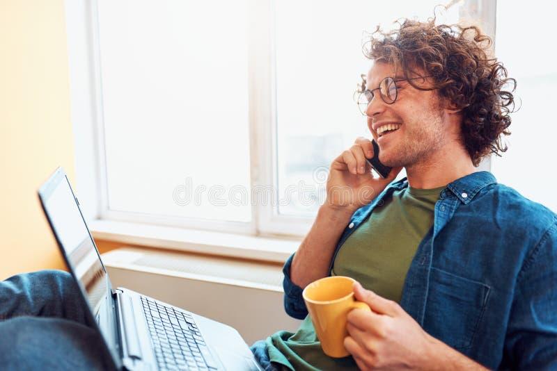 Zijaanzicht van gelukkige jonge mensenzitting in het bureau die op mobiele telefoon spreken terwijl het werken aan laptop royalty-vrije stock foto's